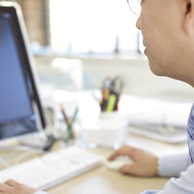 Shot in the UK, businessman wokring at computer