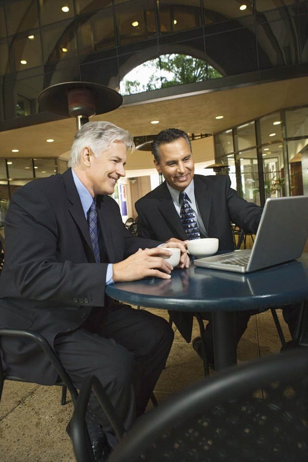 Businessmen in cafe using laptop