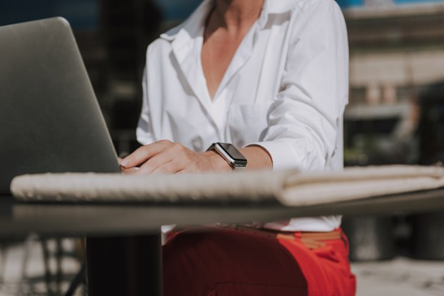 Cropped photo of businesswoman wearing white blouse and working at laptop