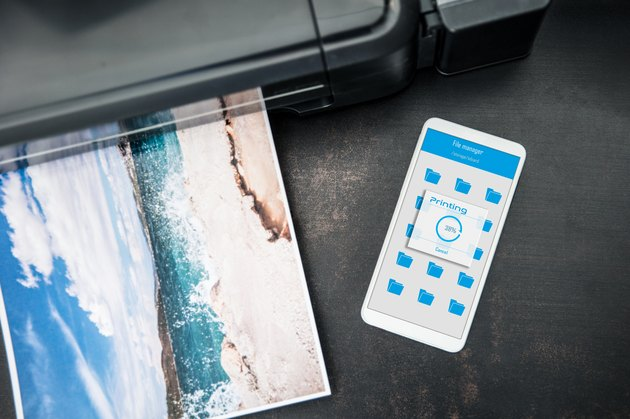 Smartphone connected to the wireless printer is laying on the desk