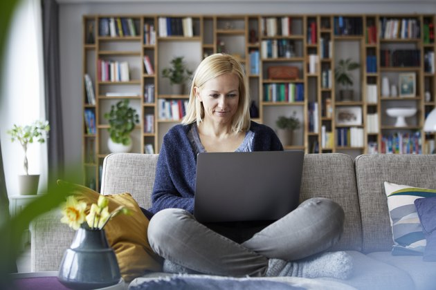 Woman at home sitting on couch using laptop