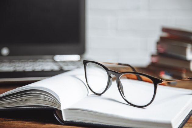 Eyeglasses on an open notebook on a wooden background.