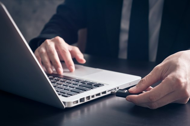 Businessman using flash drive connect to laptop