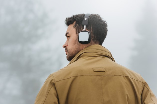 Horizontal portrait of young Caucasian man walking in foggy mountain, listening to music outside. Rear view of Caucasian man wearing trendy coat and bluetooth headphones. People, technology concept.