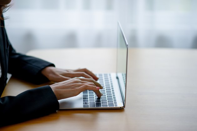 Cropped Hands Of Woman Using Laptop On Table At Home