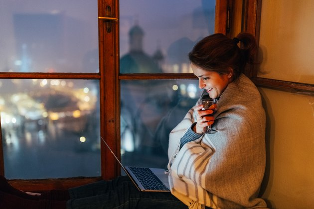 Smiling woman at home watching movie on the laptop