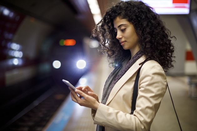 Young businesswoman standing on the subway station and using her mobile phone while waiting for the train