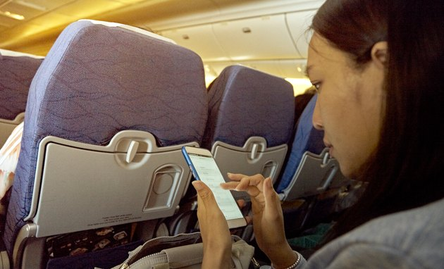 Side View Of Mid Adult Woman Using Mobile Phone While Sitting In Airplane