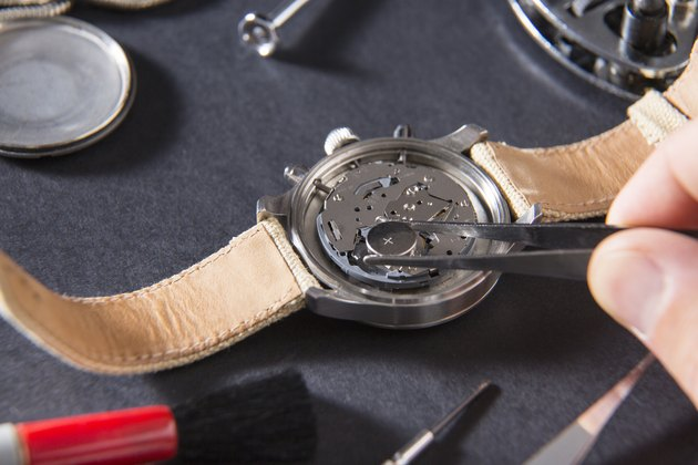 Detail of the work of a watchmaker who replaces a battery
