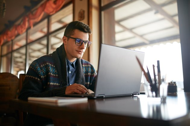 Handsome freelancer businessman working on laptop in cafe. Blogger man updating his profile in social networks with photos sharing with followers multimedia using notebook with wifi. Nerd in glasses