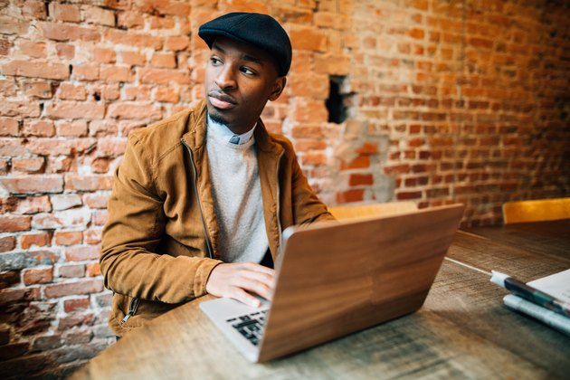 Young man sitting in coffee shop and using laptop
