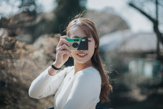 Joyful young woman taking photos with disposable camera in park on a lovely sunny day