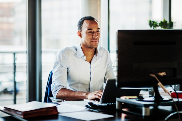 Office Manager Working On Computer At His Desk