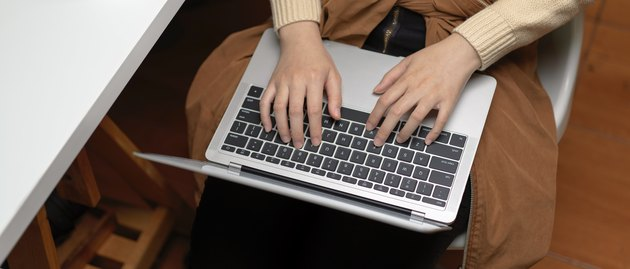 Female hands typing on laptop on her lap while sitting on office chair in office room