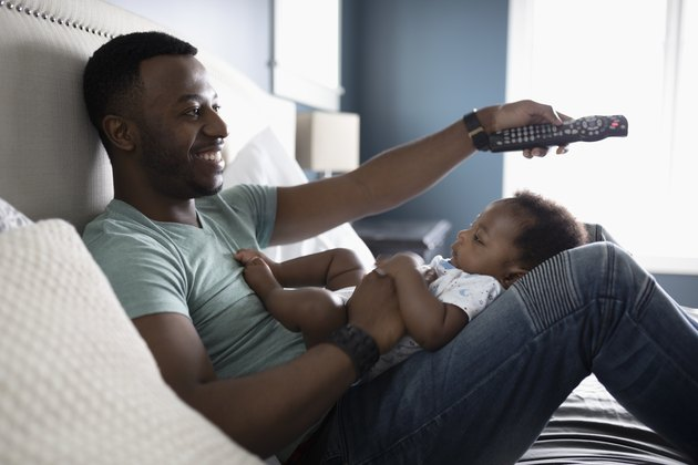 Smiling father with remote control watching TV with baby son in lap on bed
