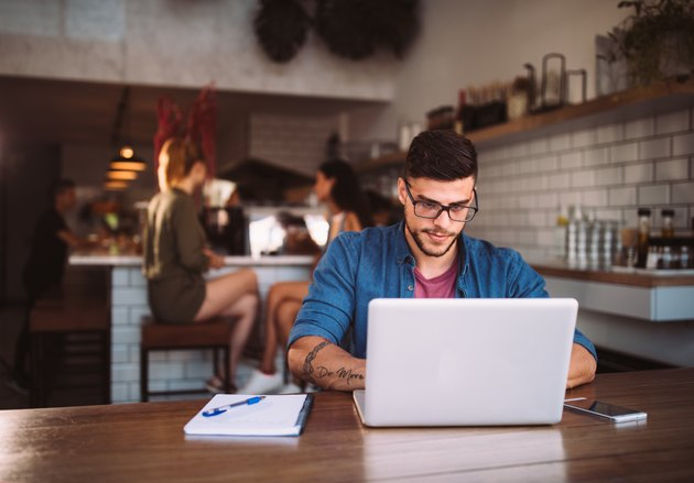 Young hipster businessman working on laptop at urban coffee shop