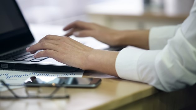 Hands of female office employee typing on laptop, enters survey data, closeup