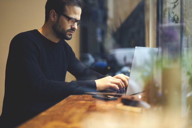 Serious journalist sitting at wooden table using modern devices and searching important information in internet. Student writing article keyboarding text message and concentrated looking at screen