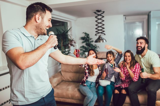 Group of friends playing karaoke at home