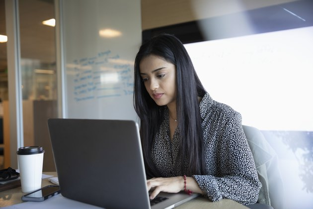 Focused businesswoman using laptop in conference room