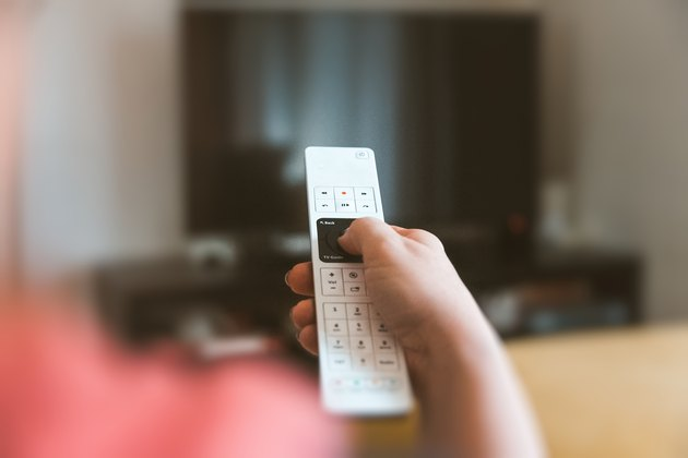 Cropped Hand Using Television Set Remote Control At Home
