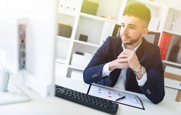A young man sitting in the office at a computer Desk and working with documents.