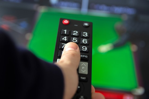 Man watching TV set and using remote control.