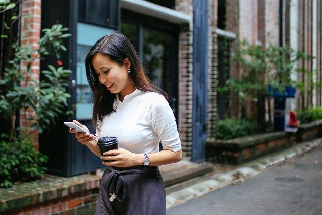 Young woman having a coffee on the go in Kuala Lumpur, Malaysia