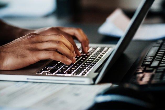 Close Up Of Man Typing On Laptop