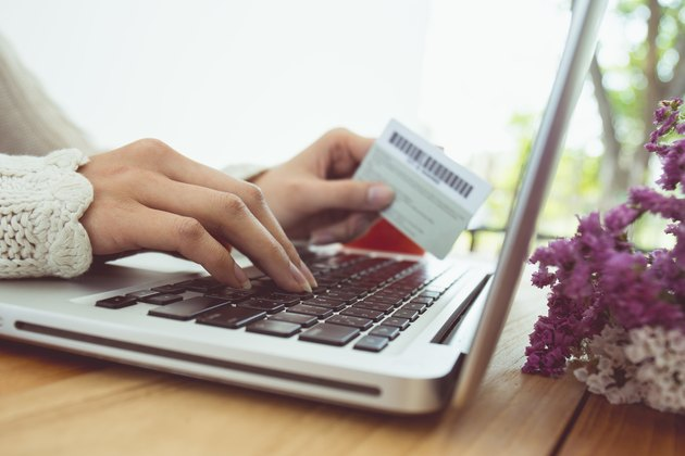 Cropped Hands Of Woman Making Card Payment While Using Laptop At Table