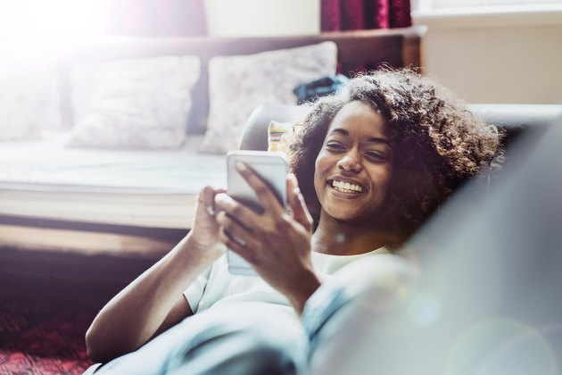 Happy woman using mobile phone on sofa