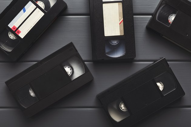 Video cassettes on gray wooden surface . Back to the past