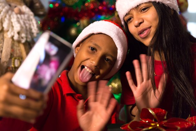 Siblings taking selfie photos during Christmas time at home