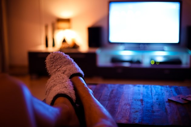 Man putting feet up and watching television