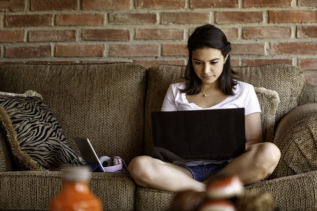 Hispanic young woman working on a laptop computer at home. Home office concepts