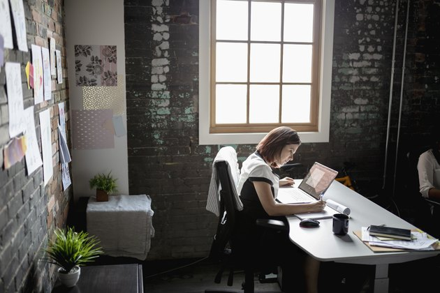 Dedicated creative businesswoman working at laptop in office