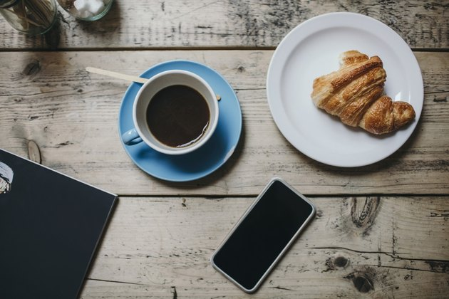 Directly above shot of smart phone with coffee and croissant on wooden table