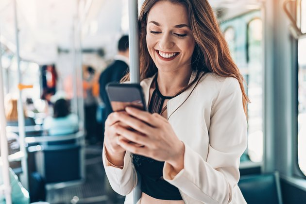 Smiling young woman with cell phone in the bus