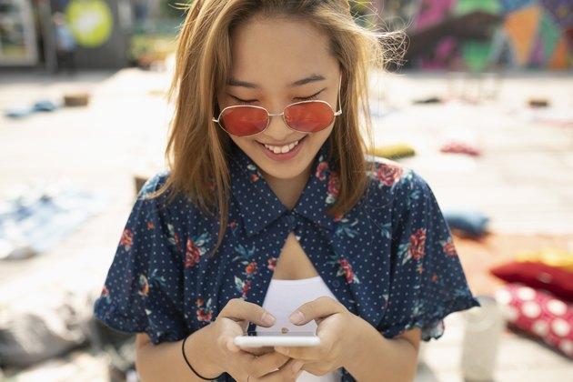 Teenage girl with sunglasses using smart phone