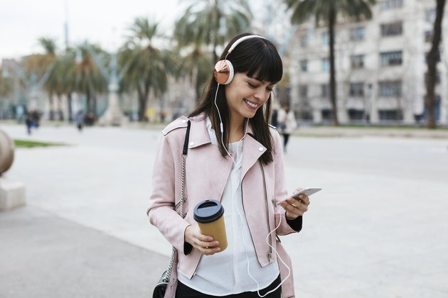 Spain, Barcelona, smiling woman with coffee, cell phone and headphones in the city