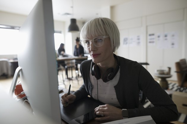 Focused female graphic designer using graphics tablet, leaning toward computer in office