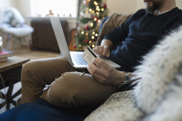 Young man with credit card online Christmas shopping on laptop