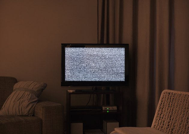 Darkened living room with static noise on TV screen
