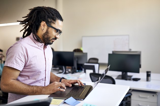 Side view of businessman with dreadlocks using laptop computer on desk in office