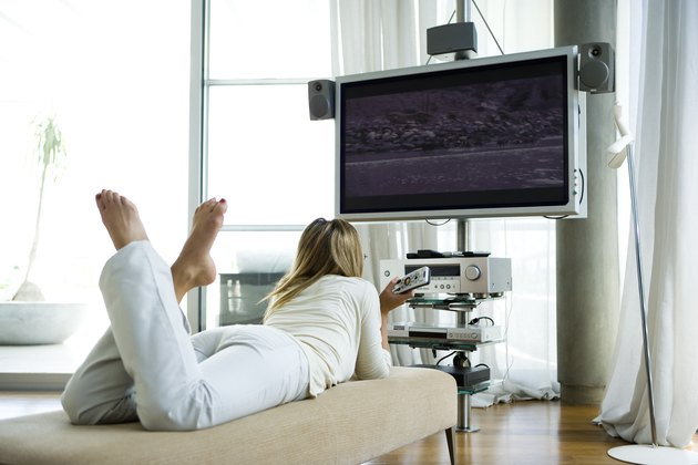 Female lying on chaise longue, watching flat screen television with surround sound