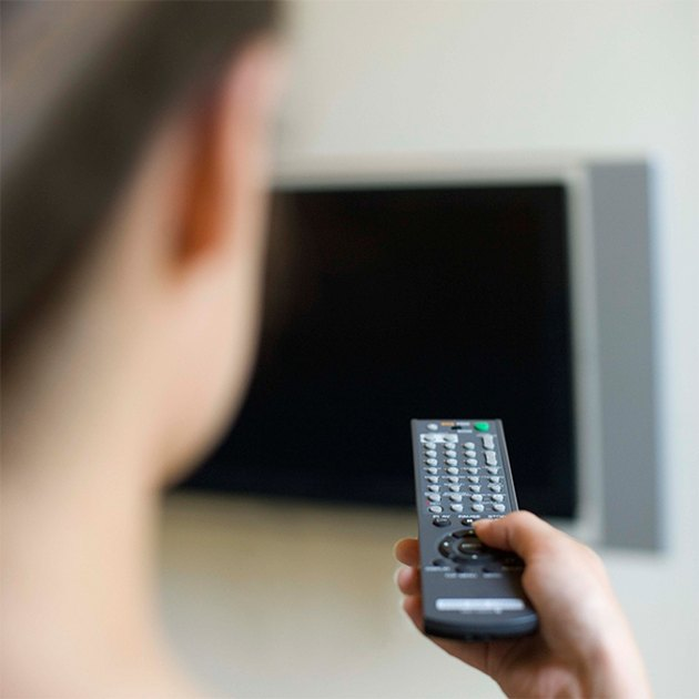 Woman using television remote control