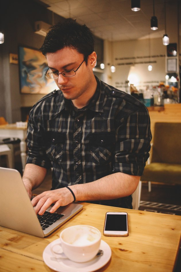 Young man sitting in a coffee shop using laptop
