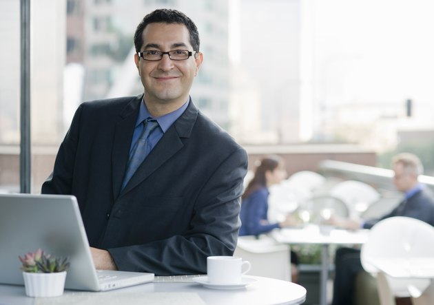 Smiling business man with computer in cafe.