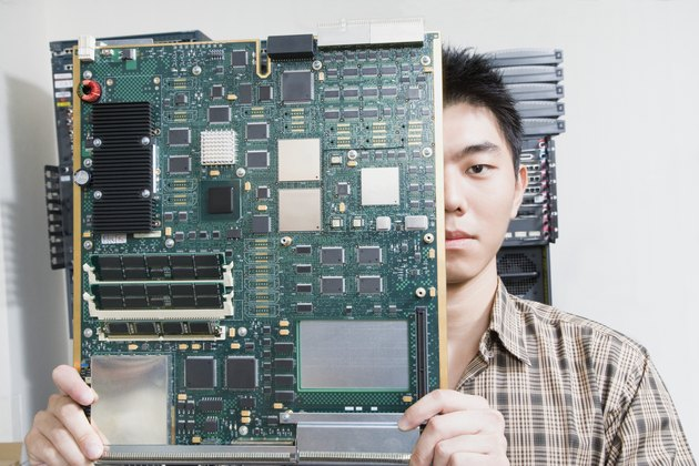 Computer technician holding motherboard