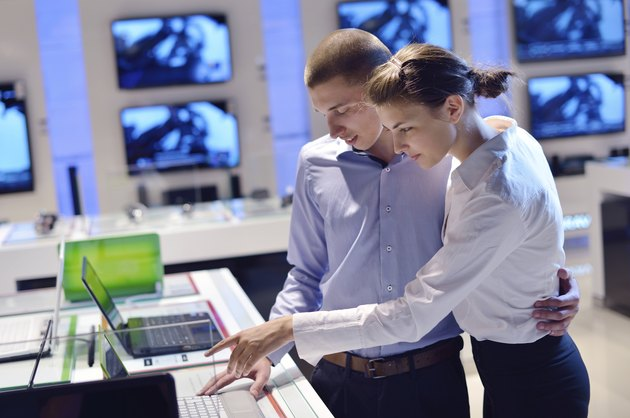 couple in consumer electronics store buying laptop